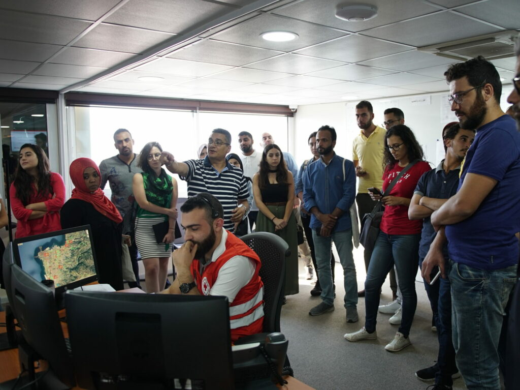 A group of people observing the work of an emergency coordinator in front of many computer screens.