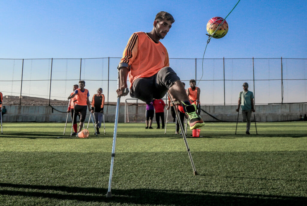 A football player with crutches hitting a ball.