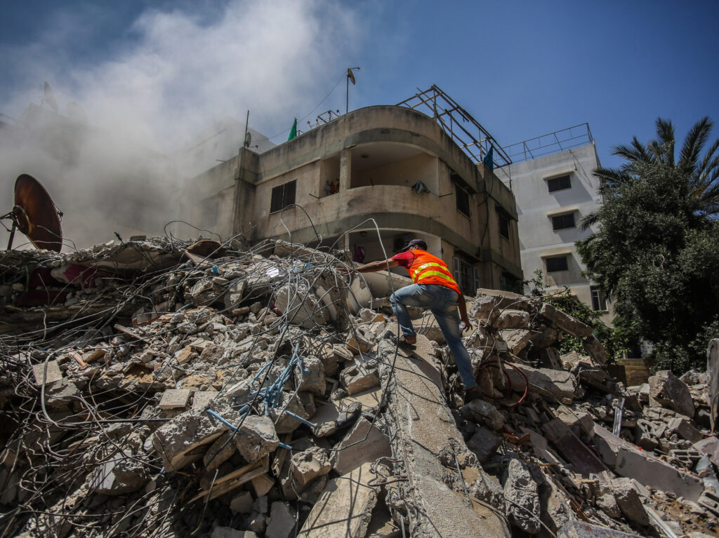 A man climbing on a pile of rubble that is still smoking after an air strike.