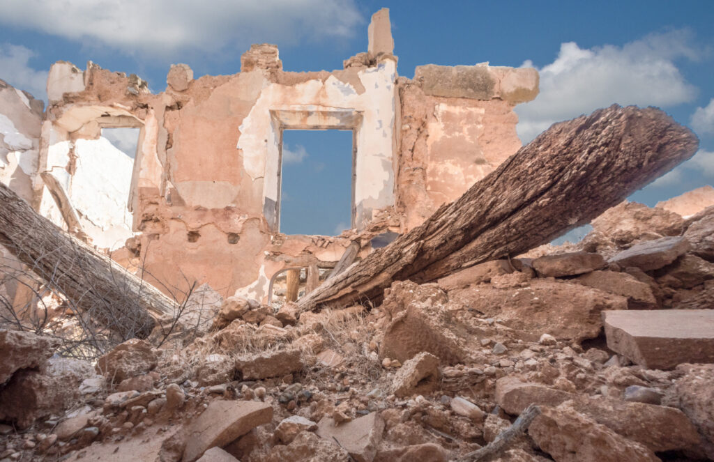 The rubble of a destroyed building and in the background a remains of a house wall.
