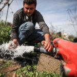 A man installs a water pipeline on a field.