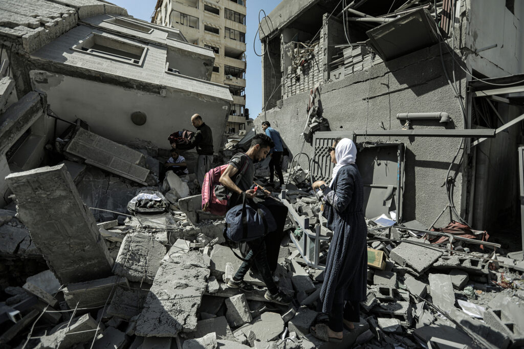 People climbing over the rubble of a destroyed building.