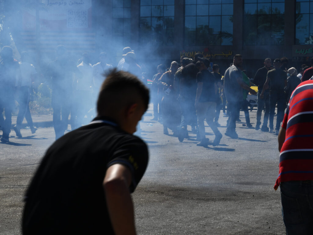 The silhouette of a group of demonstrators in the smoke.