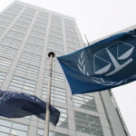 Blue flags of the International Criminal Court in front of the Court's office tower.