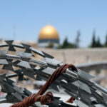 Barbed wire and in the background the golden dome of the Dome of the Rock in Jerusalem.