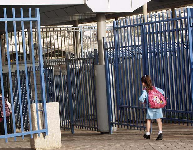 A girl walking through a high metal gate.