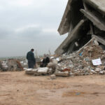 A man and a woman in front of destroyed building.