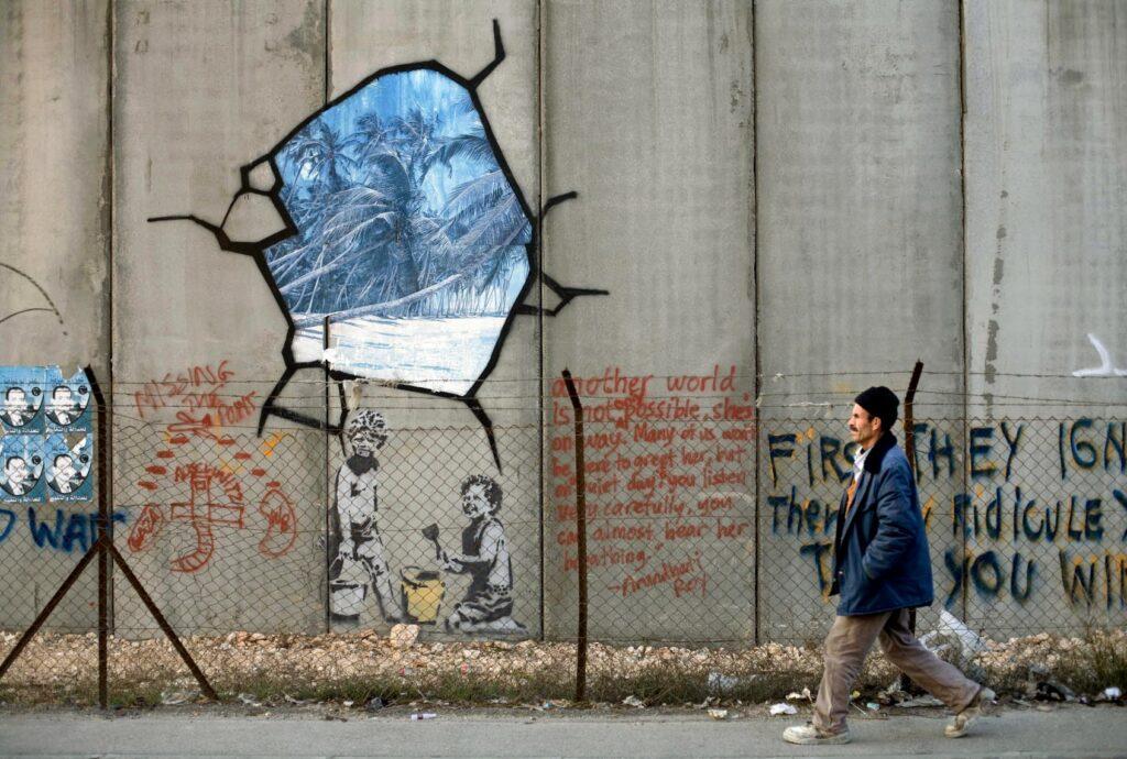 A man passes graffiti on a high wall.
