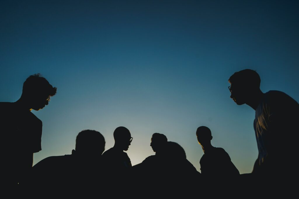 Silhouettes of people in a blue sky.