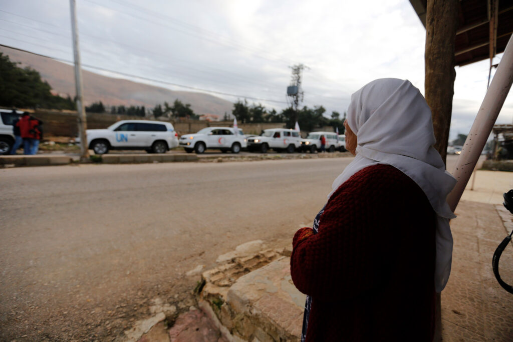A woman watching United Nations vehicles, as part of a humanitarian convoy.