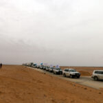 A convoy of cars with United Nations flags driving through dry land.