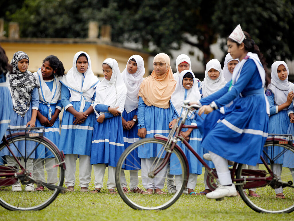 A big group of girls riding bicycles.