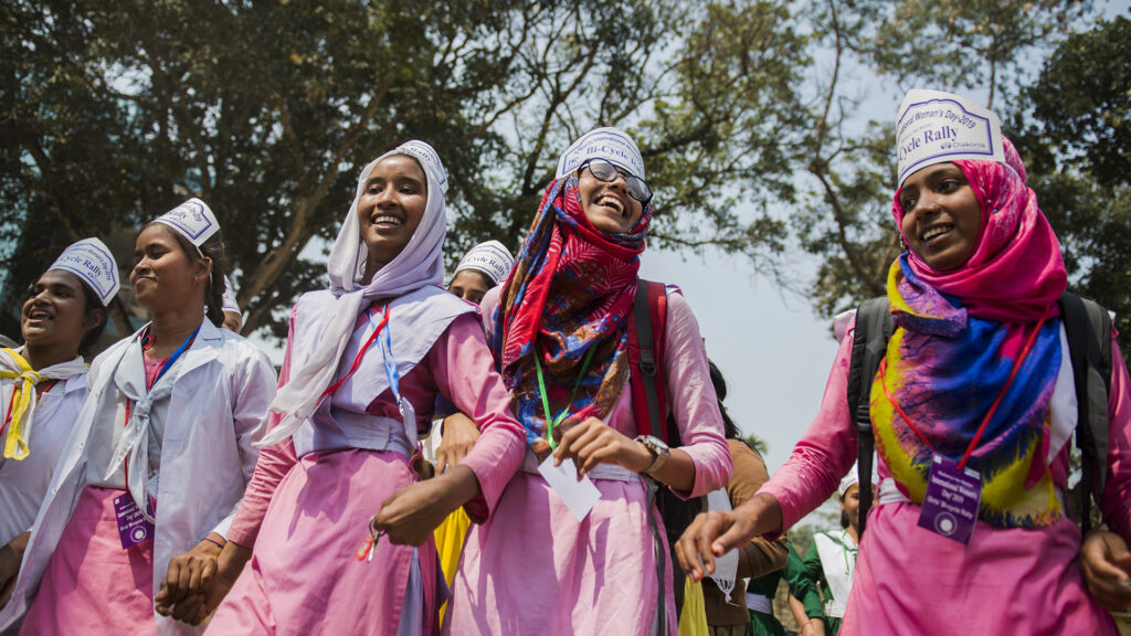 A group of young women at a manifestation. They are jolding hands and smiling.