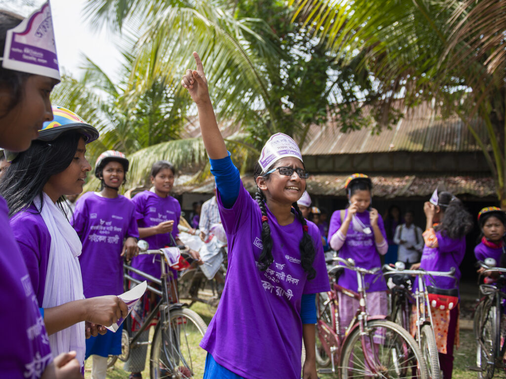 A group of girls at a bicycle rally in Bangladesh. One girl is lifting her hand up.