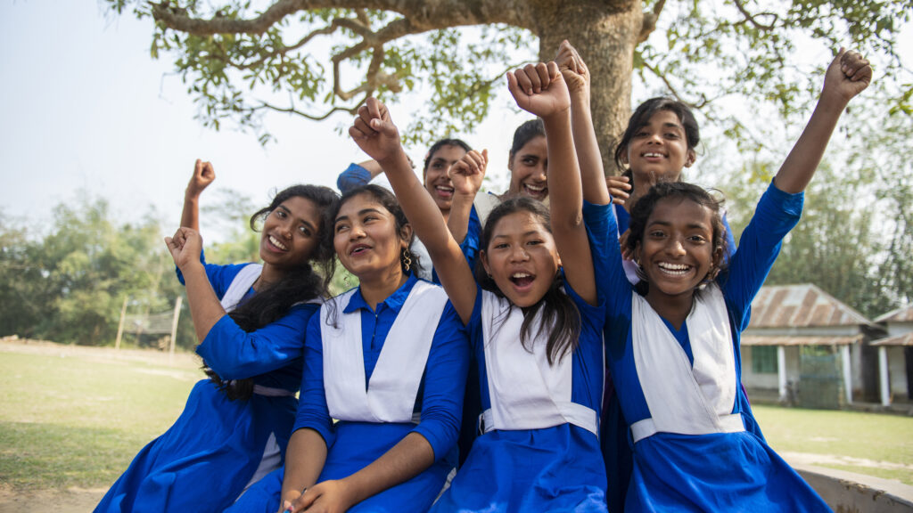 A group of girls in school uniforms sitting next to a tree. They are lifting their hands up.