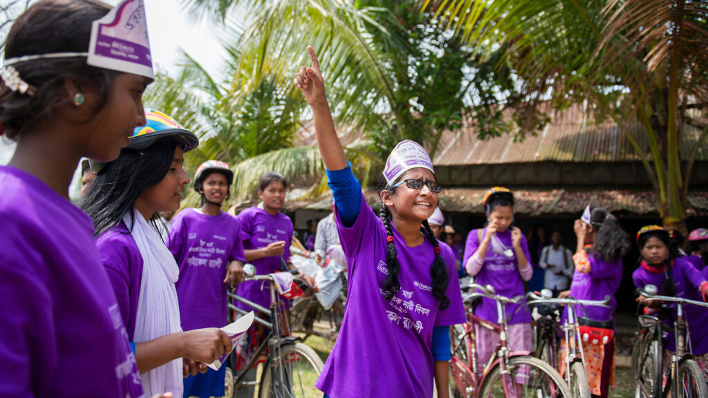 A group of young women in Bangladesh at a bicycle rally. The women are wearing the same purple t-shirts.