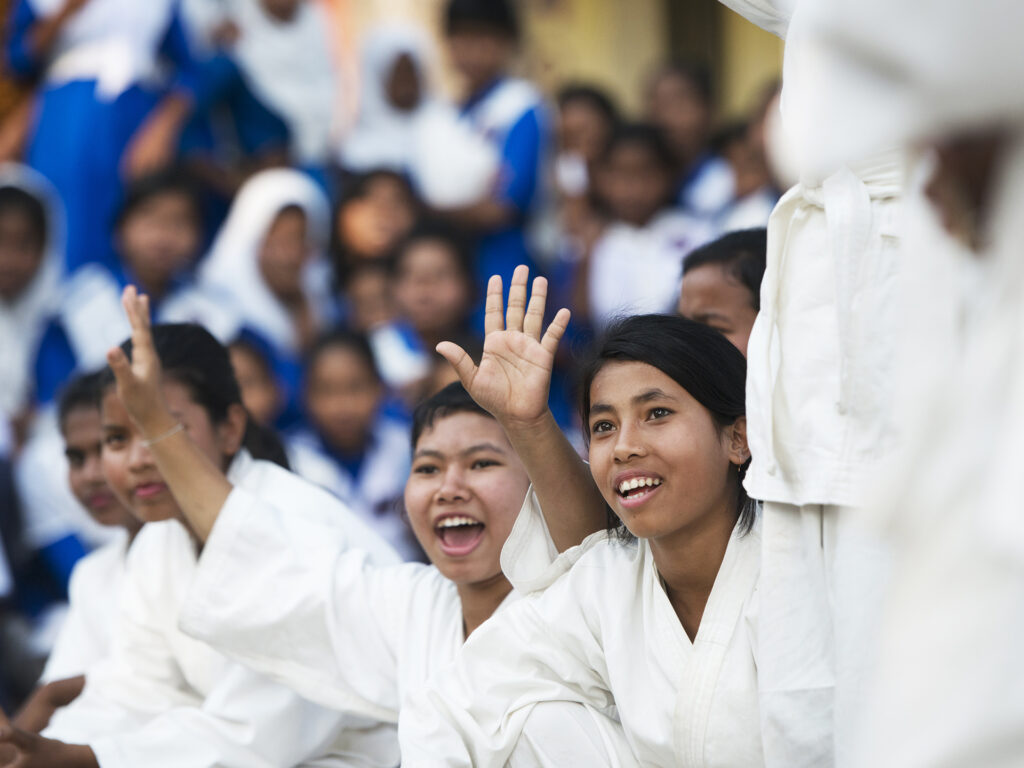 Young women in Karate suits sitting in a group cheering.