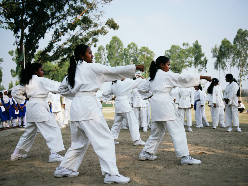 A large group of young women in white karate suits, standing in karate positions.