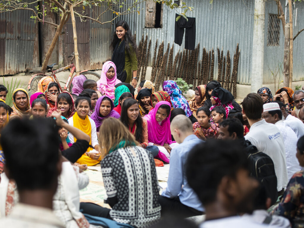 A gathering with a big group of people, sitting on the ground.