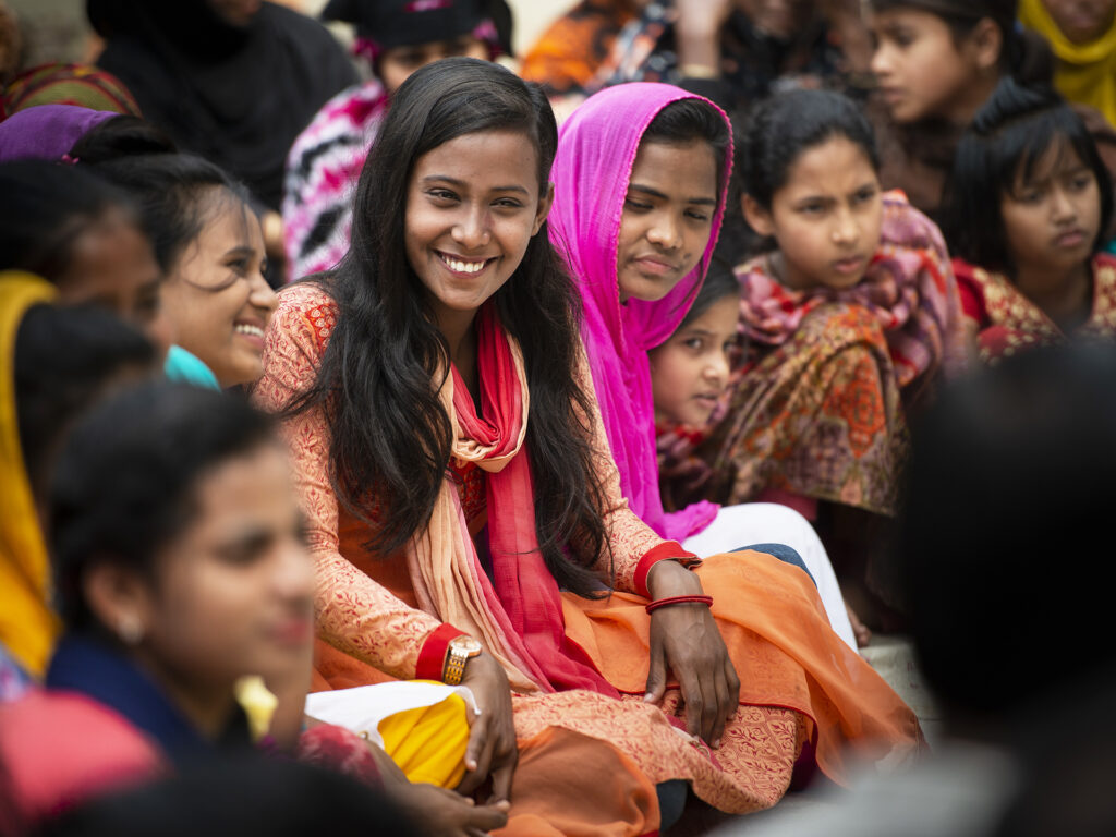 A woman sitting in a crowded group of people, smiling.