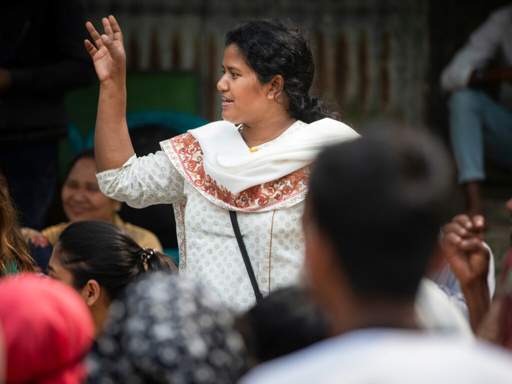 A woman standing in a group of people, gesticulating and talking.