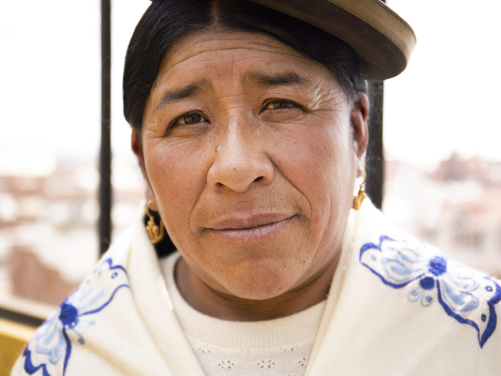 A closeup of a Bolivian woman wearing the traditional hat.