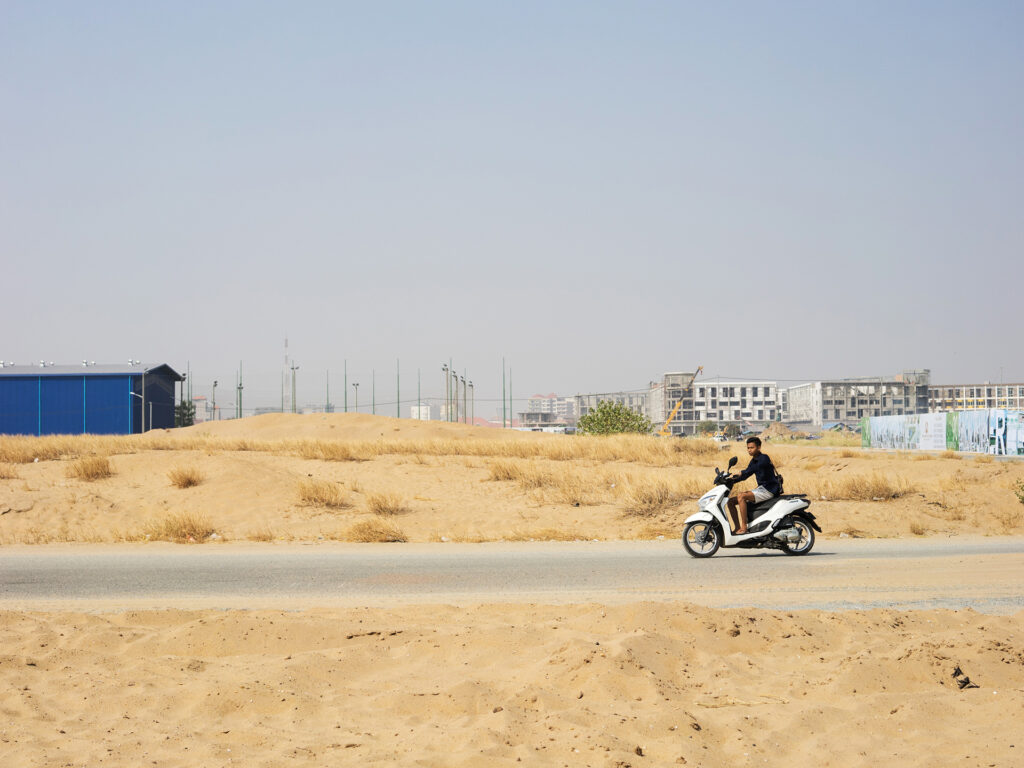 A man on a motorcycle dricing through a wide landscape.