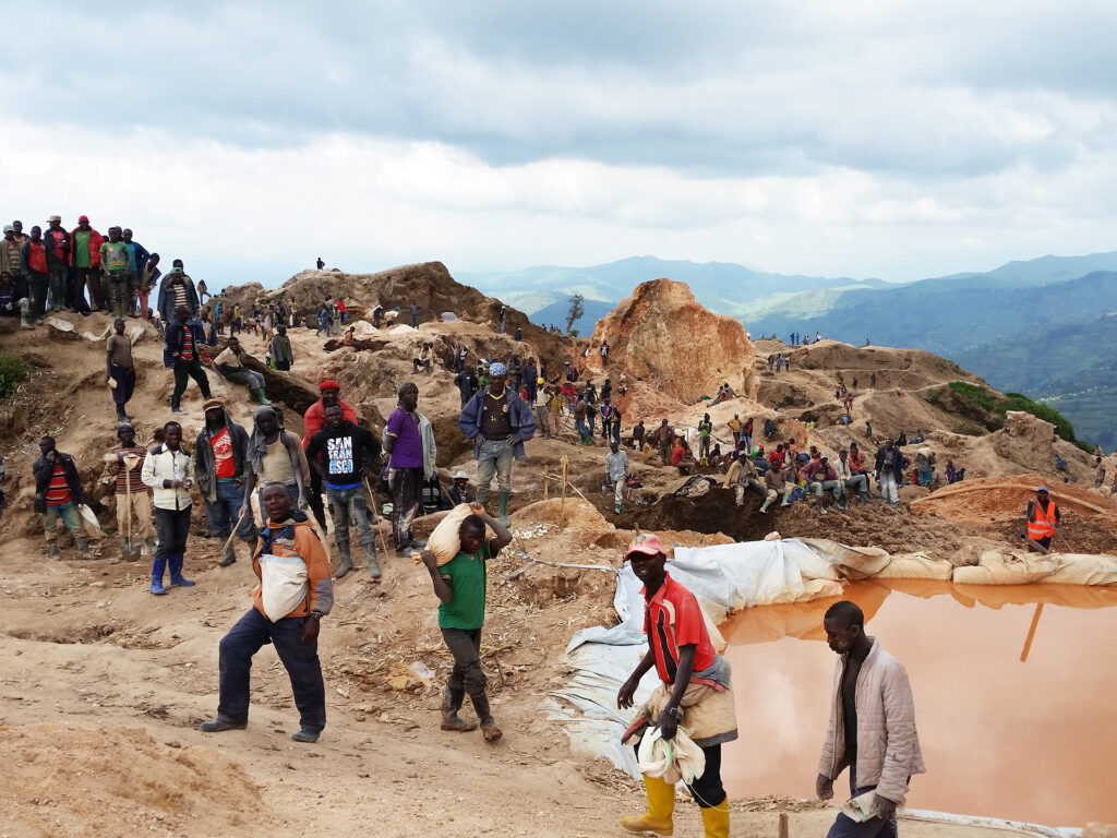 A large group of people in a field alongside mines.
