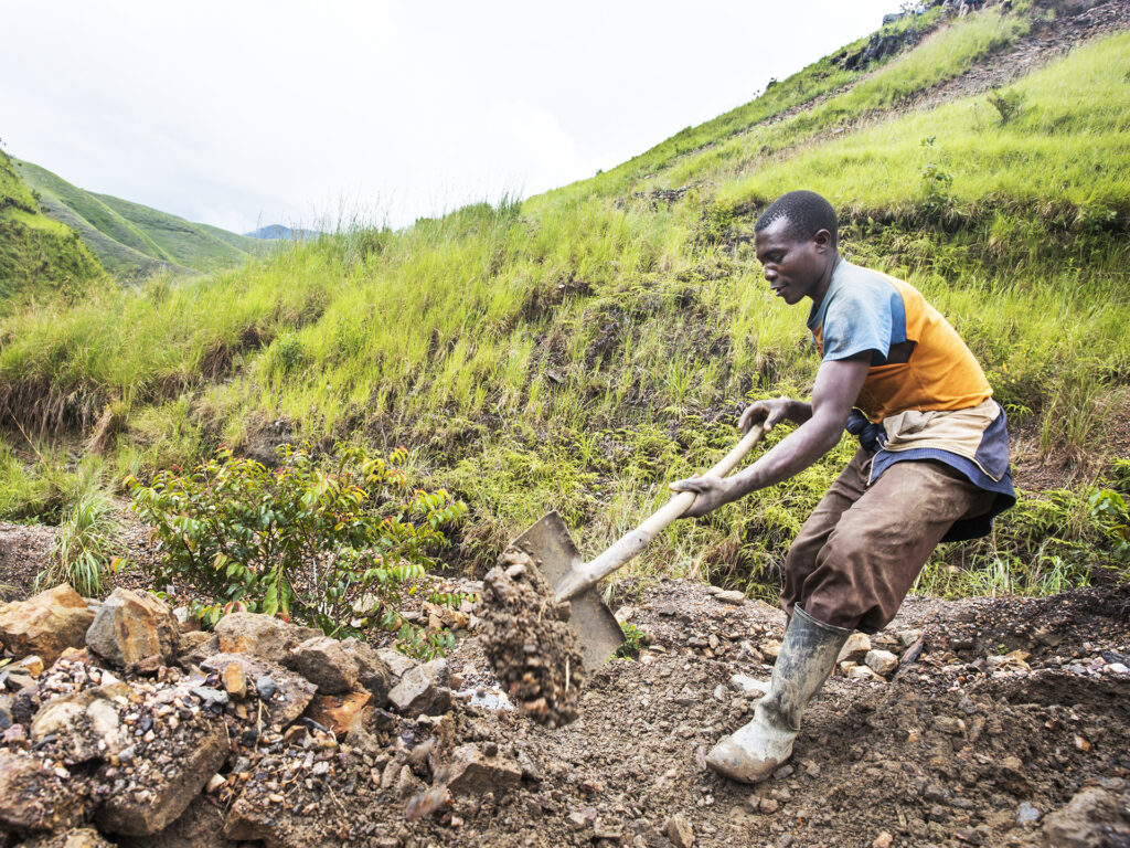 A Congolese man using a shovel in a field.