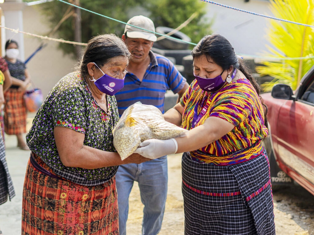 Two Guatemalan women wearing face masks handling food packages