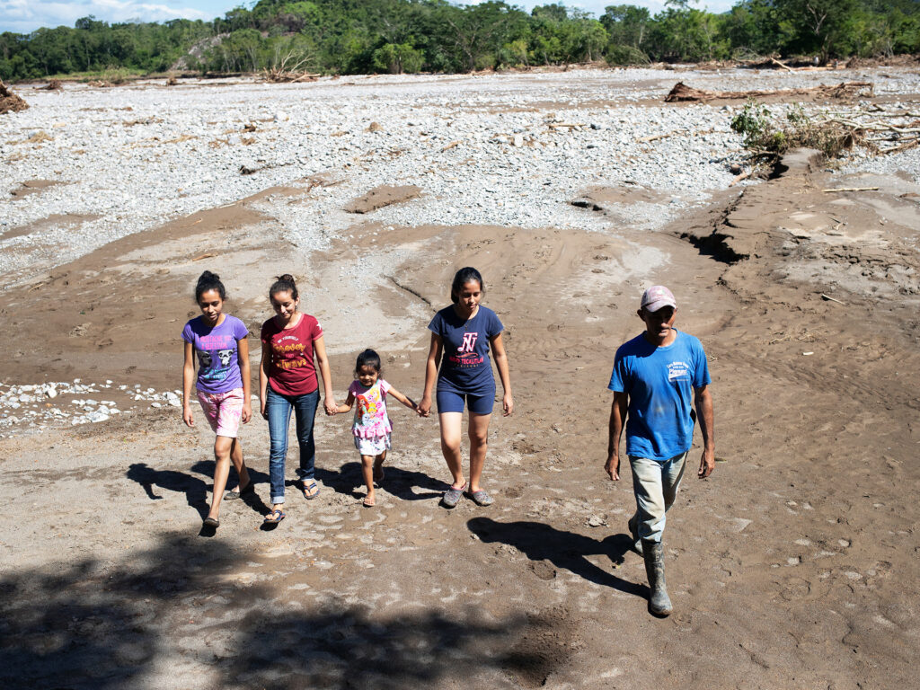 A group of people, adults and children, walking on sandy ground.