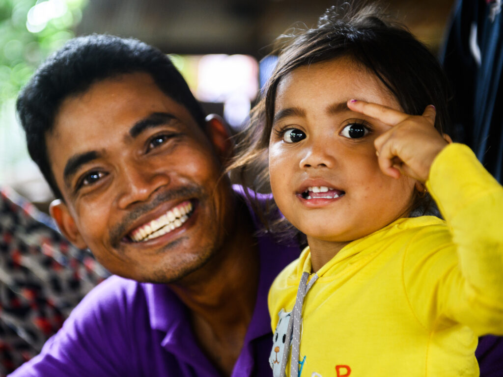 A closeup of a smiling Cambodian father next to his young daughter.