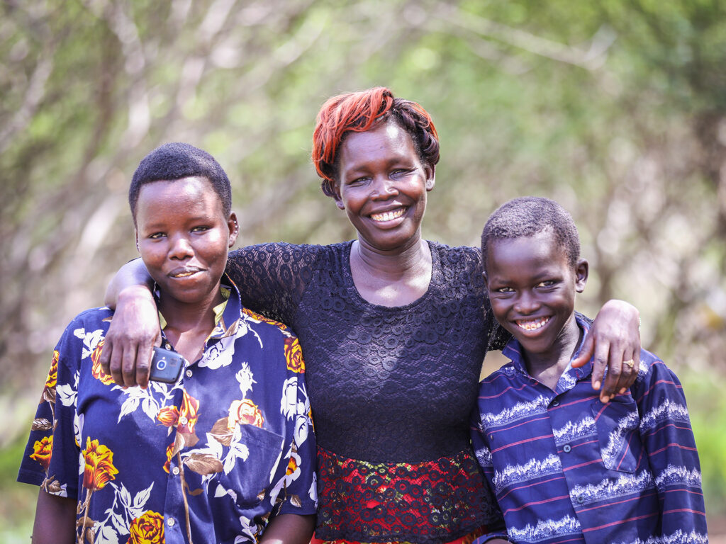 Kenyan mother holding her arms around two children with trees in the background.