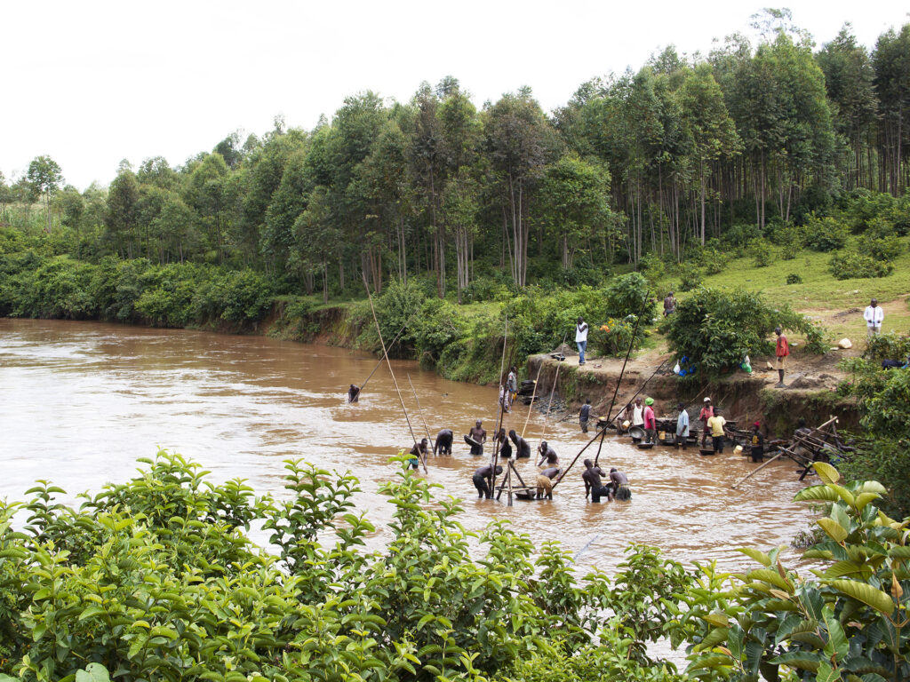 A view over a lake in Kenya and a forest, there are people working by the water.