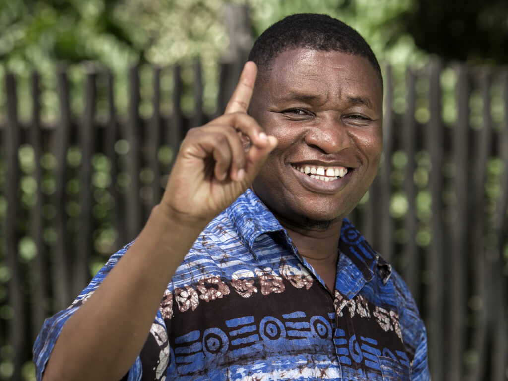 A smiling Kenyan man with his finger lifted, looking in to the camera.