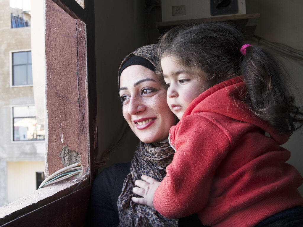 A Palestine woman and her child looking out through a window