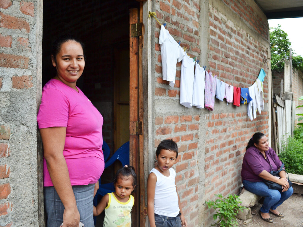 A Nicaraguan woman standing outside a house with two kids.