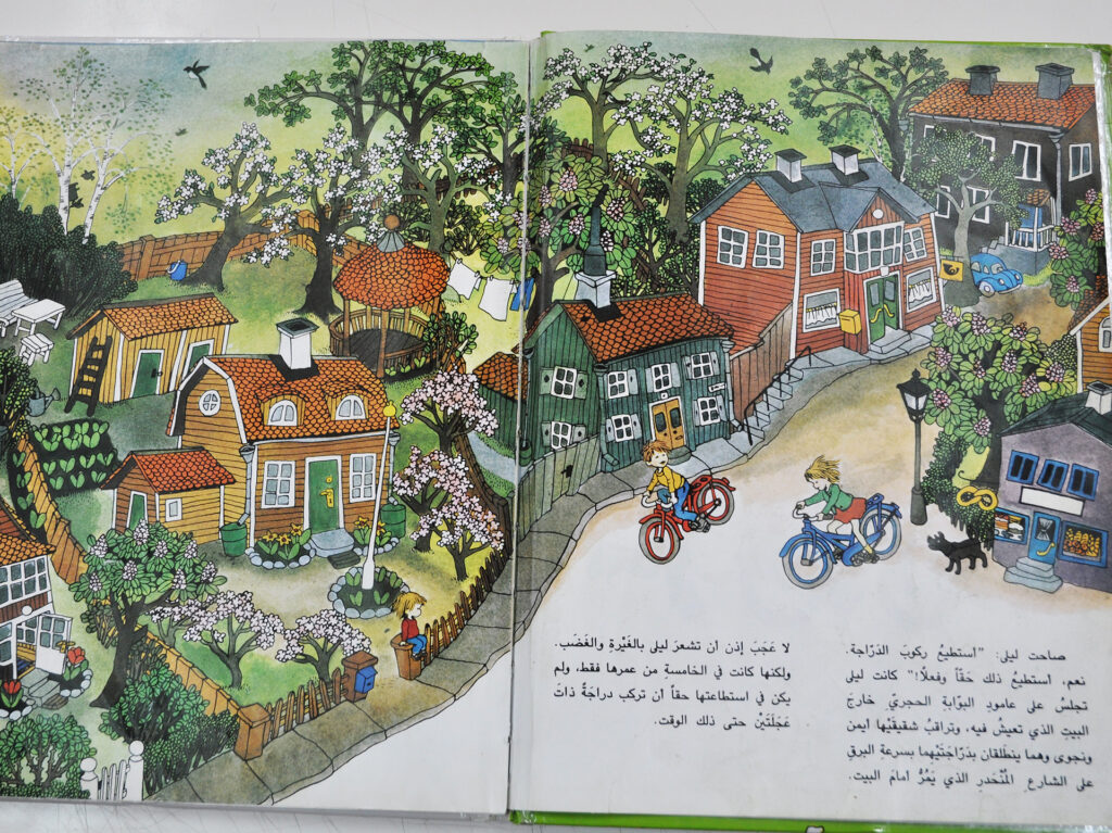 An open children's book with colorful illustrations and text in Arabic.