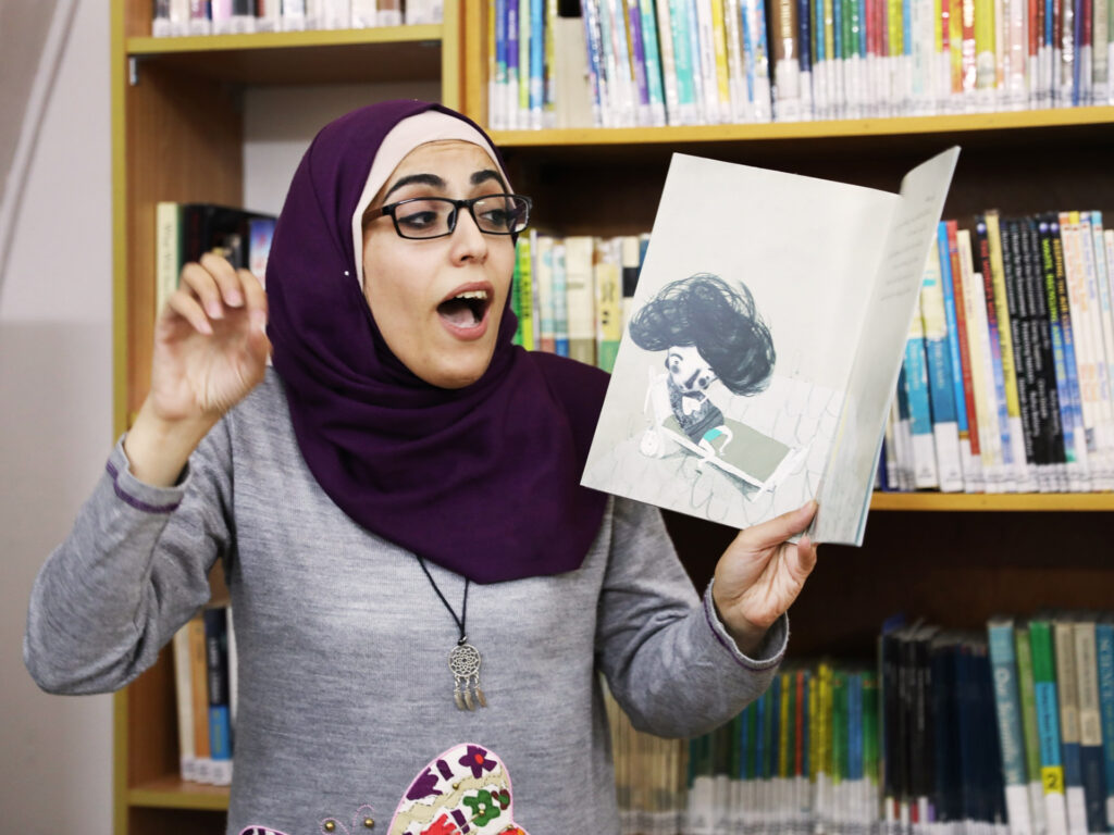 A woman reading loud from a childrens book at a library.