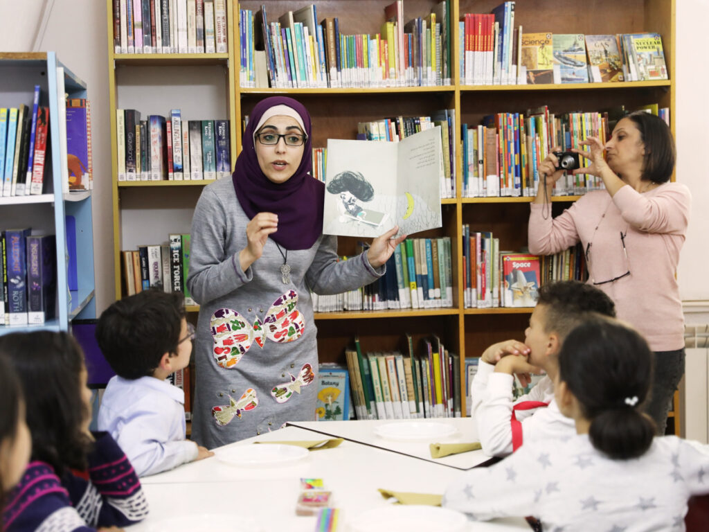 A teacher reading a childrens book to a group of children in a library