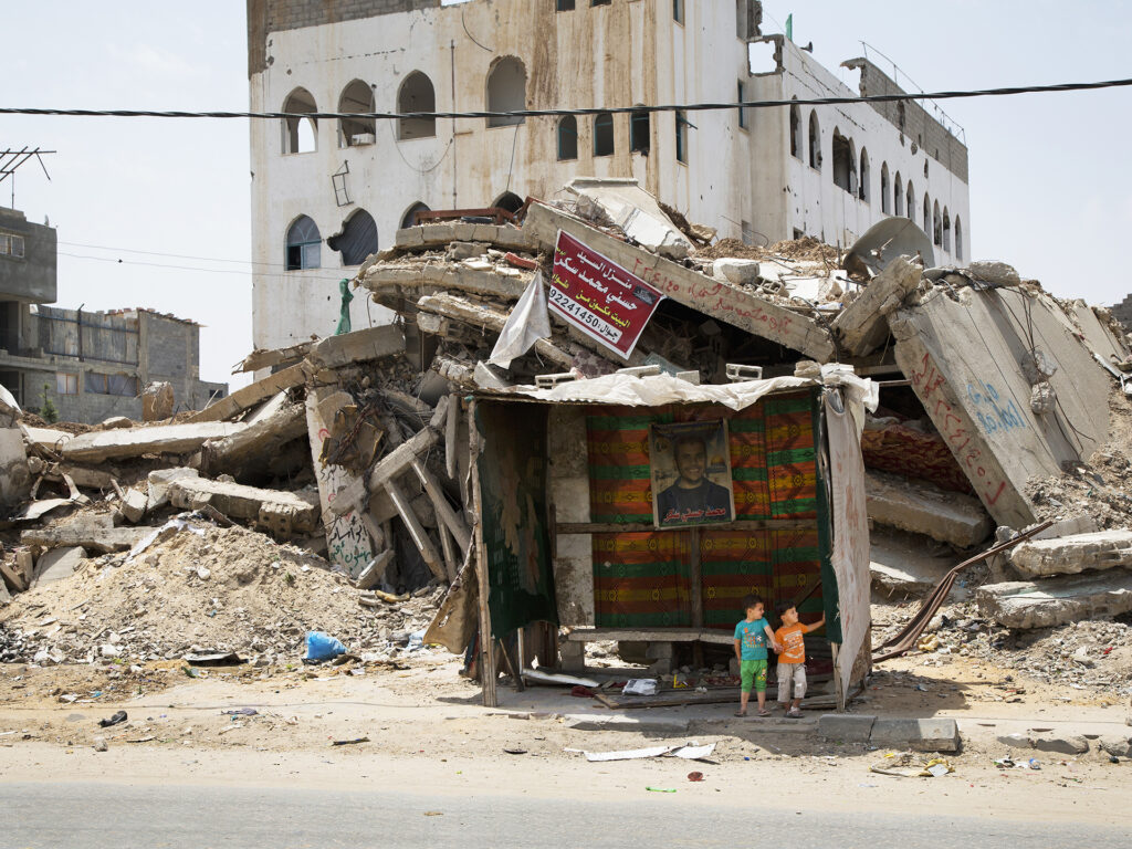 Bombed houses in Gaza. Two kids are sitting in a booth.