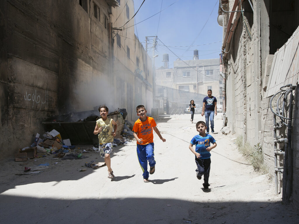 Children running in the streets of a refugee camp