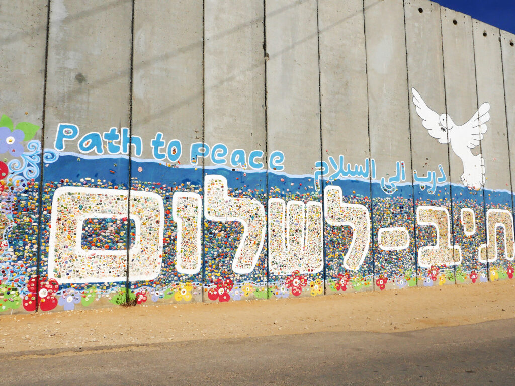 """Image of a concrete wall with a mural that says """"Path to peace""""."""