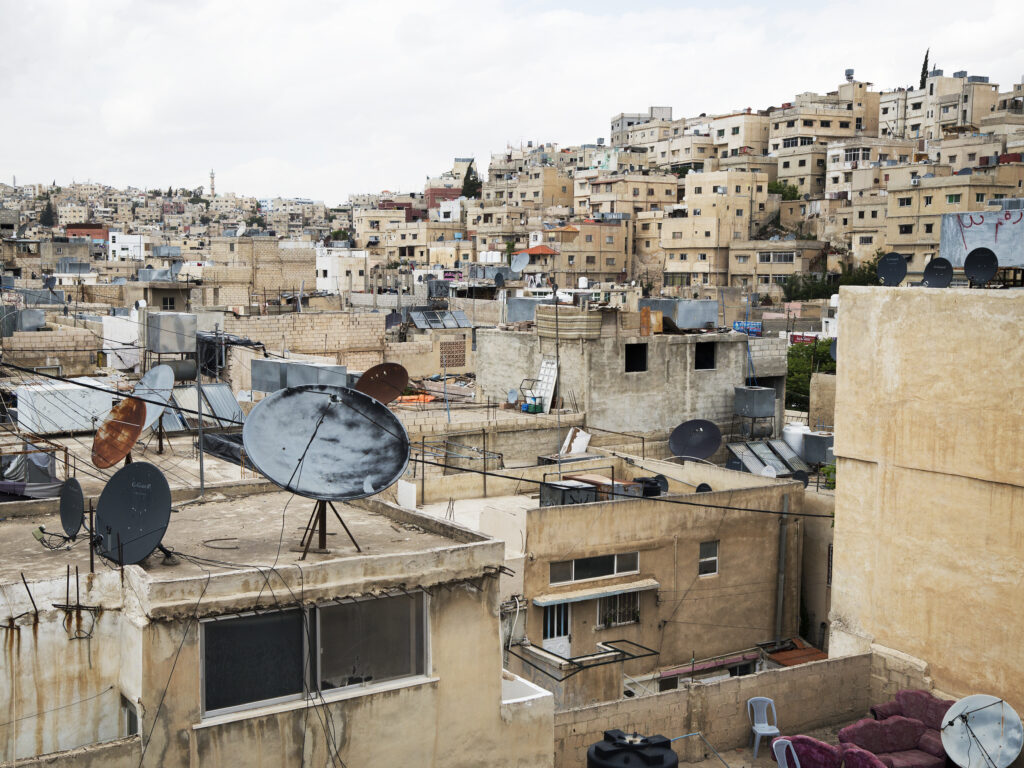 A view of a refugee camp in Palestine, with a lot of houses and a hill.