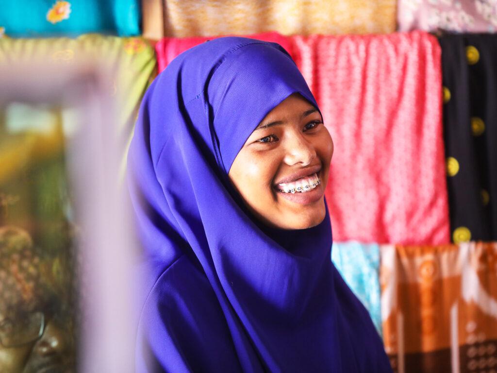 A smiling Somali woman wearing a purple hijab.