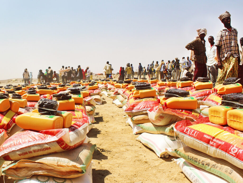 Large bags of food lying in a desert. In the background there is a lot of people.