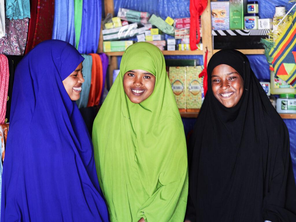 Three somalian women wearing hijab inside a shop.
