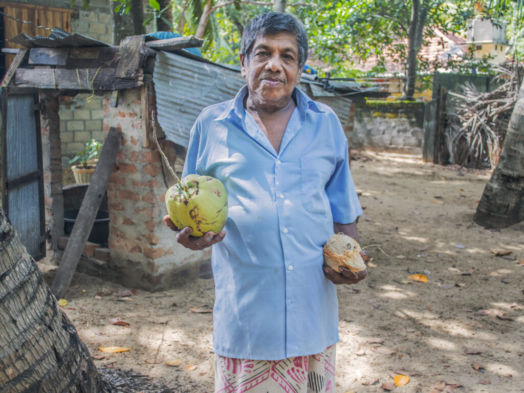 A man carrying two big fruits.
