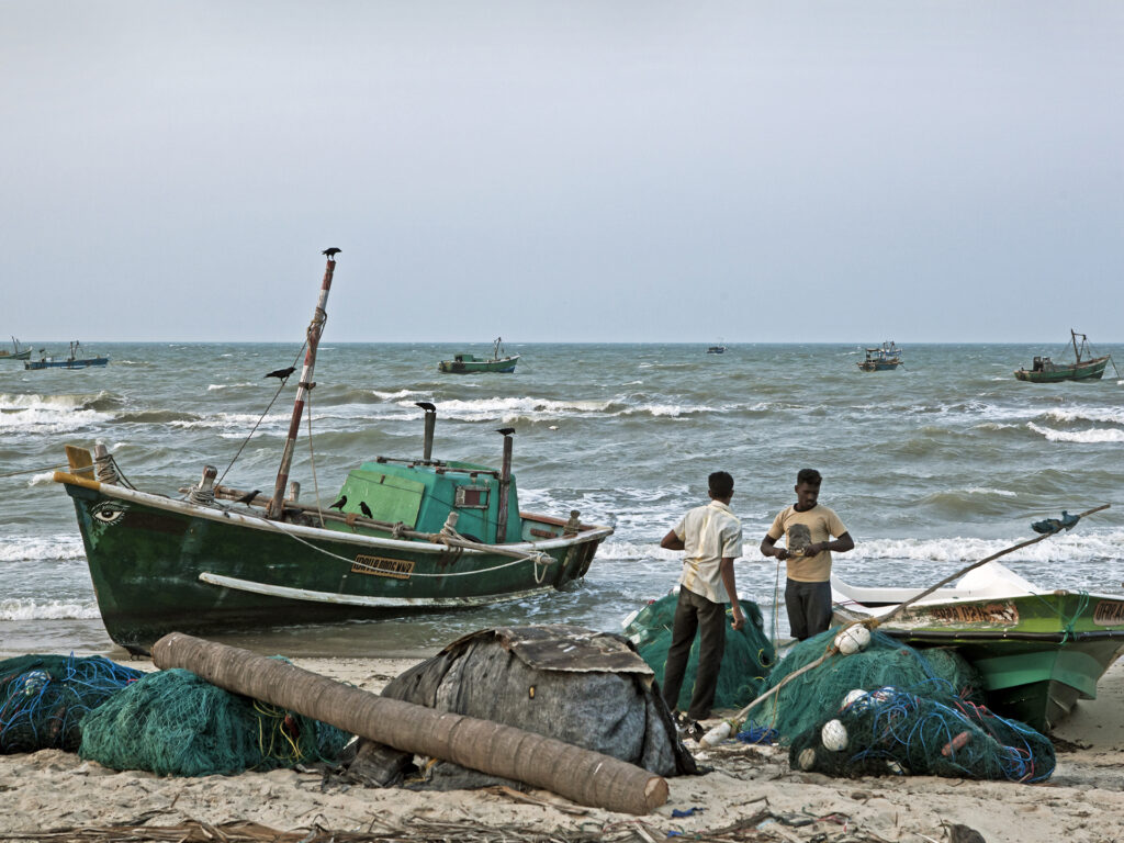 Two fishermen and a boat at the beach.