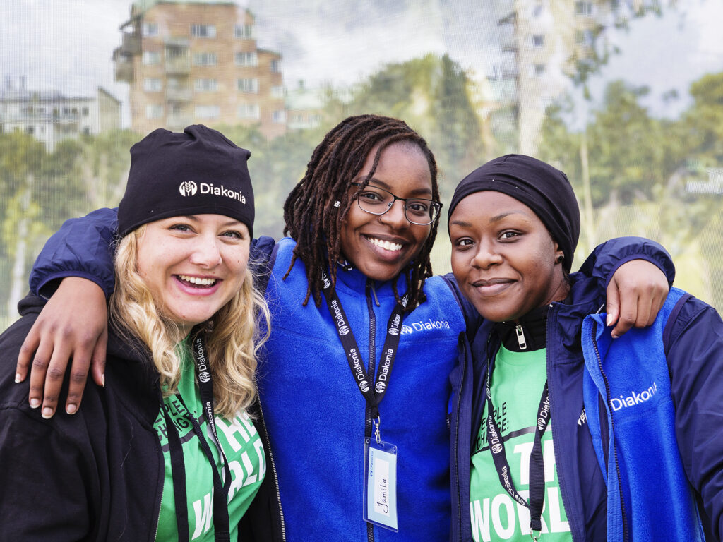 Three women wearing Diakonia jackets and hats, looking into the camera and smiling.
